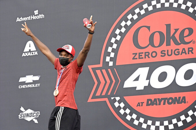 Olympic bronze medalist Noah Lyles acknowledges the crowd after being introduced as the grand marshal before a NASCAR Cup Series auto race at Daytona International Speedway, Saturday, Aug. 28, 2021, in Daytona Beach, Fla. (AP Photo/Phelan M. Ebenhack)