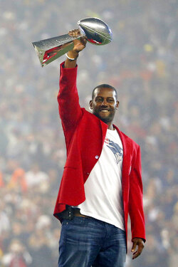 FILE - In this Sept. 10, 2015, file photo, former New England Patriots cornerback Ty Law raises one of the Patriots Lombardi Trophies before an NFL football game between the New England Patriots and the Pittsburgh Steelers, in Foxborough, Mass. Law will be inducted into the Pro Football Hall of Fame in Canton, Ohio on Aug. 3, 2019. (AP Photo/Winslow Townson, File)