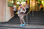 A member of the Thai Royal Police walk out of the Century Plaza mall Tuesday, Feb. 18, 2020 in Bangkok, Thailand. Gun violence has struck again at a shopping mall in Thailand, where a man in the nation's capital Bangkok shot dead one woman working in a beauty clinic and wounded another. (AP Photo)