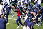 Seattle Seahawks quarterback Russell Wilson (3) reaches for a ball as he runs through a drill with teammates Thursday, Aug. 13, 2020, in a practice during an NFL football training camp in Renton, Wash. (AP Photo/Elaine Thompson)