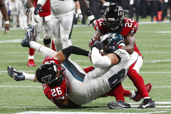Philadelphia Eagles tight end Zach Ertz (86) is stopped for a first down by Atlanta Falcons free safety Isaiah Oliver (26) Atlanta Falcons strong safety Keanu Neal (22) during the second half of an NFL football game, Sunday, Sept. 15, 2019, in Atlanta. The Atlanta Falcons won 24-20. (AP Photo/John Bazemore)