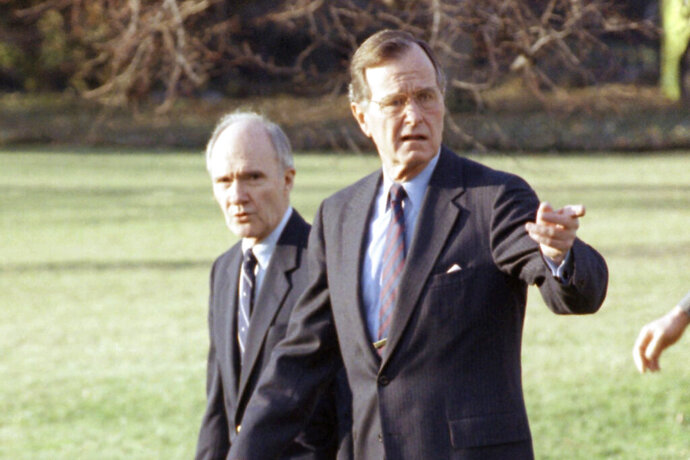 FILE - In this Feb. 6, 1990 file photo, President George H. W. Bush gestures as he and National Security Adviser Brent Scowcroft walk to the presidential helicopter on the South Lawn of the White House in Washington. (AP Photo/Barry Thumma)