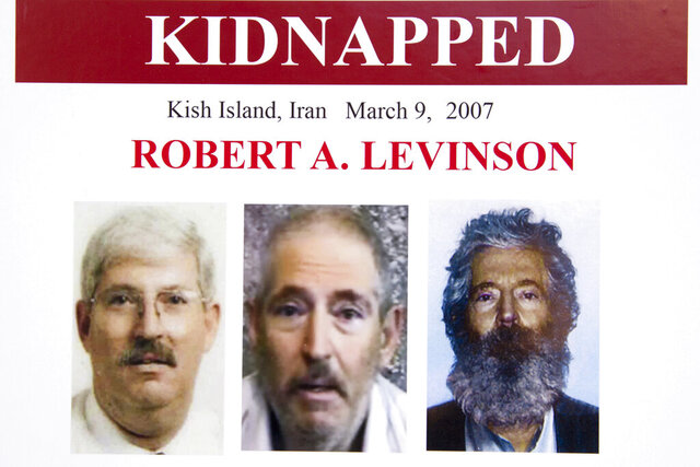 FILE - In this March 6, 2012, file photo, an FBI poster showing a composite image of former FBI agent Robert Levinson.  At right, is a photo of how he would look like after five years in captivity, and an image, center, taken from the video, released by his kidnappers, and a picture before he was kidnapped, left, displayed during a news conference in Washington.  The U.S. government is for the first time formally blaming Iran for the presumed death of retired FBI agent Robert Levinson. Officials on Monday publicly identified two Iranian intelligence officers believed responsible for his abduction. (AP Photo/Manuel Balce Ceneta, File)