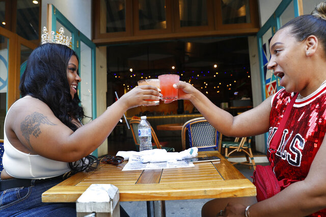 Maya Evans, right, toasts friend Tifffany Webster, 30, on Webster's 30th birthday during the first day of the city's phase two reopening from the coronavirus outbreak, Monday, June 22, 2020, on the Upper West Side of Manhattan in New York. Under phase two, the city's restaurants are allowed to serve patrons for outdoor dining with some precautions and restrictions. (AP Photo/Kathy Willens)