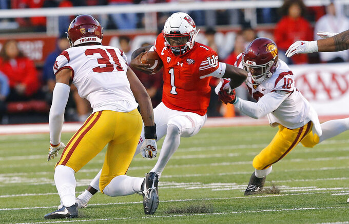 Utah quarterback Tyler Huntley (1) is tackled by Southern California's Hunter Echols, left, and John Houston Jr., center, during the first half of an NCAA college football game Saturday, Oct. 20, 2018, in Salt Lake City. (AP Photo/Rick Bowmer)