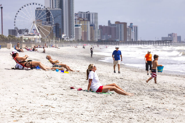 Sun bathers and walkers visit the 2nd Avenue Pier area of Myrtle Beach, S.C. on Wednesday, April 29, 2020. Public beach accesses have re-opened in Myrtle Beach after being closed for weeks due to the coronavirus. (Jason Lee/The Sun News via AP)