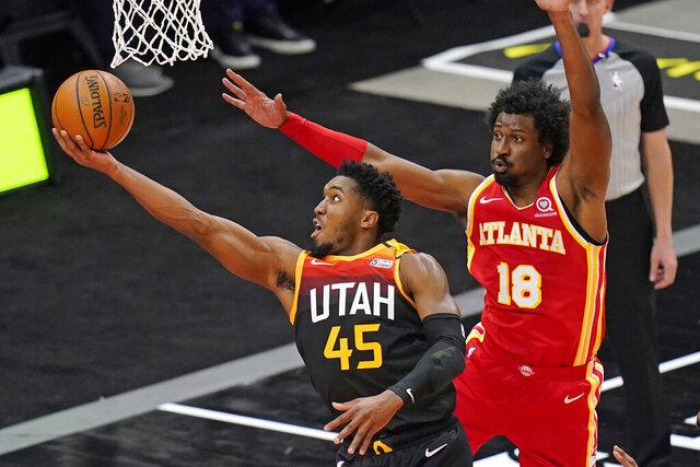 Utah Jazz guard Donovan Mitchell (45) lays the ball up as Atlanta Hawks forward Solomon Hill (18) defends during the first half of an NBA basketball game Friday, Jan. 15, 2021, in Salt Lake City. (AP Photo/Rick Bowmer)