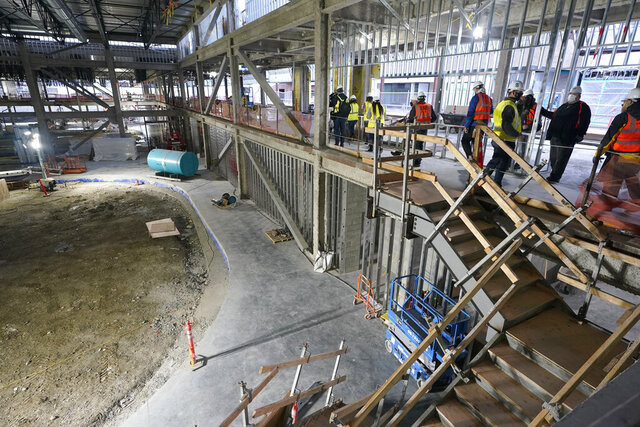 Reporters and photographers walk in an area that will house a large bar overlooking an NHL regulation ice rink, Tuesday, Nov. 10, 2020, during a media tour of the training center for the Seattle Kraken hockey team in Seattle. The building will house three NHL regulation ice rinks, and will serve also serve as the headquarters for the team. (AP Photo/Ted S. Warren)