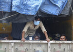 Migrant workers sit inside a truck, after they were stopped and directed towards a temporary shelter to register for free travel on a train, during lockdown to prevent the spread of new coronavirus on the outskirts of Hyderabad, India, Saturday, May 16, 2020. Tens of thousands of migrant laborers have been returning from big cities to their villages after losing jobs because of a countrywide lockdown imposed in late March to contain the spread of the coronavirus. (AP Photo/Mahesh Kumar A.)
