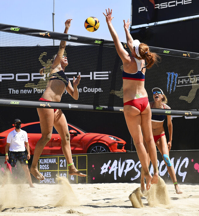 This Aug. 2, 2020, photo provided by the Association of Volleyball Professionals shows Alix Klineman, left, and April Ross, far right, during a match against Kelly Claes, foreground, and Sarah Sponcil, not shown, at the AVP Champions Cup in Long Beach, Calif. Ross was 24 years old when she first started playing beach volleyball, the sport that would eventually send her to four Olympics. At that age,  Sponcil is already headed to the Summer Games. Sponcil and her 25-year-old partner, Claes, are the first generation to come up through an NCAA beach volleyball program that didn't exist until 2012 — long after Ross graduated from Southern California. They are the youngest U.S. beach team ever to qualify for the Olympics. (Robert Beck/AVP via AP)