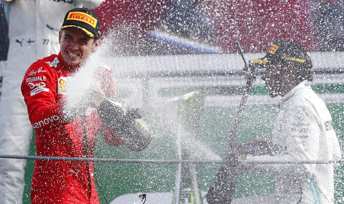 Ferrari driver Charles Leclerc of Monaco, left, celebrates with third placed Mercedes driver Lewis Hamilton of Britain, on podium after winning the Formula One Italy Grand Prix at the Monza racetrack, in Monza, Italy, Sunday, Sept.8, 2019. (AP Photo/Antonio Calanni)