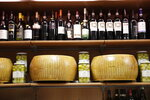 Wheels of parmesan cheese are on sale with spirits in a deli in Rome, Thursday, Oct. 3, 2019. The U.S. had prepared for Wednesday's ruling and already drawn up lists of the dozens of goods it would put tariffs on. They include EU cheeses, olives, and whiskey, as well as planes, helicopters and aircraft parts in the case _ though the decision is likely to require fine-tuning of that list if the Trump administration agrees to go for the tariffs. (AP Photo/Alessandra Tarantino)