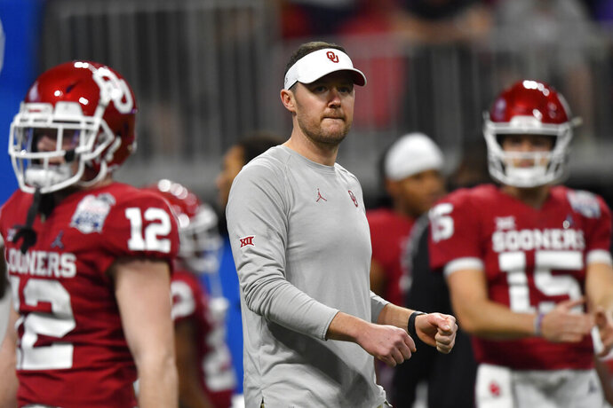 FILE - In this Saturday, Dec. 28, 2019, file photo, Oklahoma head coach Lincoln Riley speaks with his team before the first half of the Peach Bowl NCAA semifinal college football playoff game against LSU, in Atlanta. Riley already has coached Heisman Trophy winners Baker Mayfield and Kyler Murray along with Heisman runner-up Jalen Hurts. Now, he is hoping to build a new tradition at Oklahoma - pulling top quarterbacks to Oklahoma from the high school ranks. Caleb Williams, the No. 1 quarterback in the 247Sports Class of 2021 and ESPN's No. 1 dual-threat quarterback for that class, has committed to OKlahoma.(AP Photo/John Amis, File)