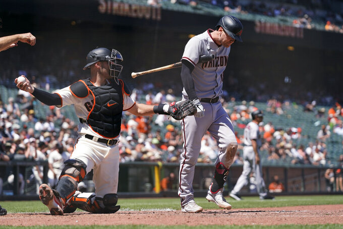 Arizona Diamondbacks' Carson Kelly walks back to the dugout after striking out swinging against San Francisco Giants starting pitcher Kevin Gausman during the seventh inning of a baseball game Thursday, June 17, 2021, in San Francisco. At left is Giants catcher Curt Casali. (AP Photo/Eric Risberg)