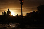 In this photo taken on Sunday, Nov. 17, 2019, a gondolier is silhouetted in a golden sunset in Venice, Italy. Venetians are fed up with what they see as an inadequate to the city's mounting problems: record-breaking flooding, damaging cruise ship traffic and over-tourism. They feel largely left to their own devices, and with ever fewer Venetians living in the historic part of the city to defend its interests and keep it from becoming a theme park or museum. (AP Photo/Luca Bruno)