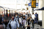 """People wear face masks to curb the spread of coronavirus as they disembark from a train during the morning rush hour at Waterloo train station in London, Wednesday, July 14, 2021. London Mayor Sadiq Khan has asked Transport for London to enforce the use of mask wearing on buses and trains as a """"condition of carriage"""", even after legal restrictions in England are lifted on July 19. Khan said he was """"not prepared"""" to put tube, tram and other transport users in the capital """"at risk"""" by removing the rules on face coverings. (AP Photo/Matt Dunham)"""