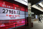 A man walks past a bank electronic board showing the Hong Kong share index at Hong Kong Stock Exchange Tuesday, May 14, 2019. Shares opened moderately lower in Asia on Tuesday after a dismal day on Wall Street as investors fled uncertainty over the China-U.S. trade standoff. (AP Photo/Vincent Yu)