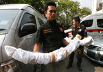 Thai officers carry illegal ivory tusks into the wildlife police headquarters in Bangkok, Thailand, Wednesday, March 14, 2018. Thai business tycoon president of Italian-Thai Development Premchai Karnasuta, currently facing nine charges including illegal hunting in a wildlife sanctuary, was further charged with illegal possession of ivory, illegal possession of firearms and attempted bribery. (AP Photo/Sakchai Lalit)