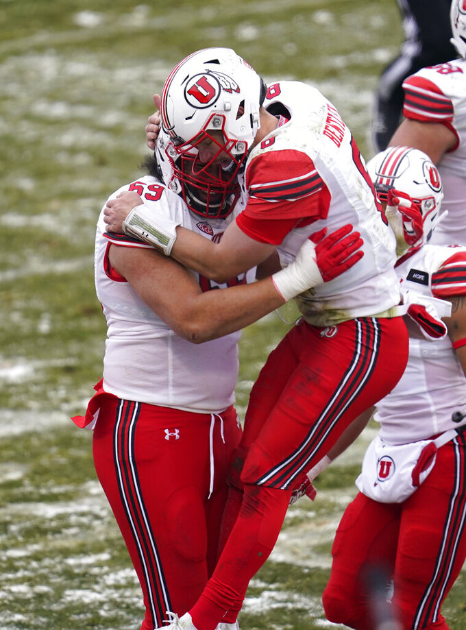 Utah quarterback Jake Bentley, right, celebrates with offensive lineman Simi Moala after a touchdown run by running back Ty Jordan in the second half of an NCAA college football game against Colorado Saturday, Dec. 12, 2020, in Boulder, Colo. Utah won 38-21. (AP Photo/David Zalubowski)