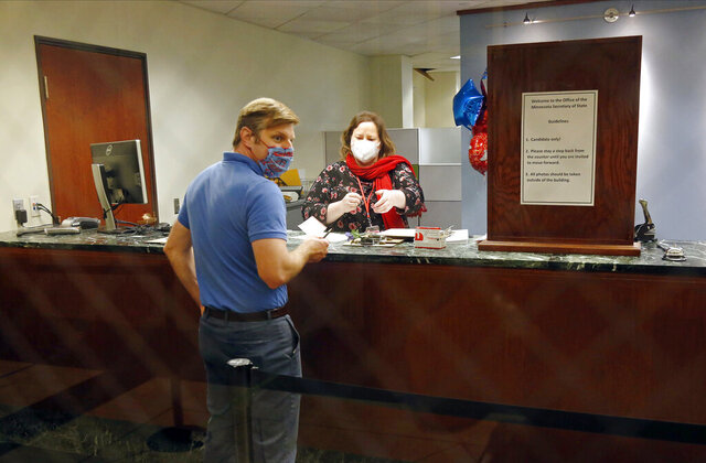 Face masks and social distancing were part of the process as election staffer Stella Hegg assists State Rep. Michael Howard as he files for re-election at the Secretary of State's Office Tuesday, May 19, 2020 in St. Paul, Minn. (AP Photo/Jim Mone)