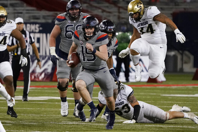 Arizona quarterback Will Plummer (15) runs away from Colorado's Nate Landman (53) and Mustafa Johnson (34) during the second half during an NCAA college football game Saturday, Dec. 5, 2020, in Tucson, Ariz. Colorado won 24-13. (AP Photo/Rick Scuteri)