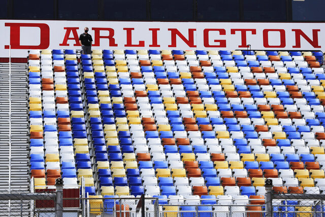 A man stands in an otherwise empty grandstand at Darlington Raceway before the Real Heroes 400 NASCAR Cup Series auto race Sunday, May 17, 2020, in Darlington, S.C. (AP Photo/Brynn Anderson)
