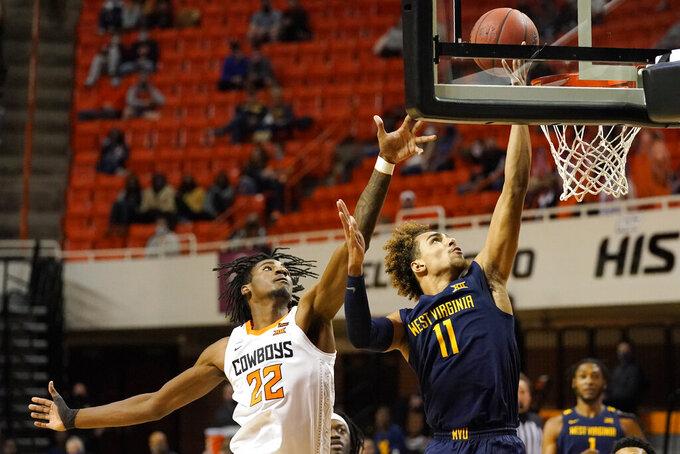 West Virginia forward Emmitt Matthews Jr. (11) shoots in front of Oklahoma State forward Matthew-Alexander Moncrieffe (12) in the first half of an NCAA college basketball game Monday, Jan. 4, 2021, in Stillwater, Okla. (AP Photo/Sue Ogrocki)