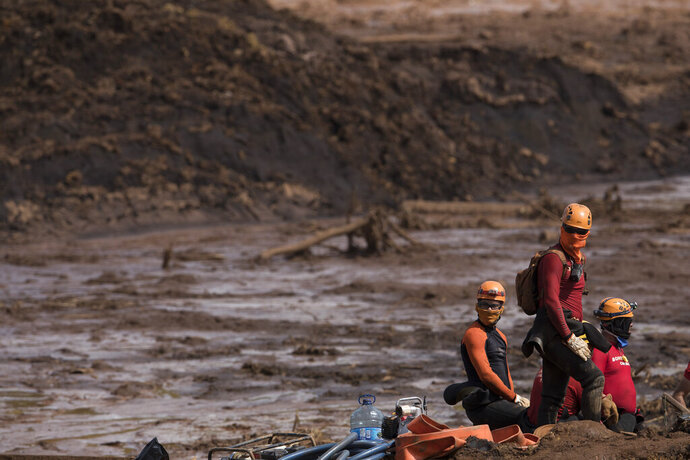 Firefighters looks on as they work on a site where a body as found inside as vehicle stuck in the mud, days after a dam collapse in Brumadinho, Brazil, Monday, Jan. 28, 2019. Firefighters on Monday carefully moved over treacherous mud, sometimes walking, sometimes crawling, in search of survivors or bodies four days after a dam collapse that buried mine buildings and surrounding neighborhoods with iron ore waste. (AP Photo/Leo Correa)