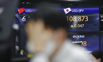 A currency trader watches computer monitors near the screens showing the foreign exchange rates at the foreign exchange dealing room in Seoul, South Korea, Thursday, April 15, 2021. Asian stock markets were mixed Thursday after Wall Street retreated from a record high as major banks reported strong profits at the start of U.S. earnings season. (AP Photo/Lee Jin-man)