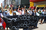 """Anti-coup protesters flashes the three-finger salute of defiance and chant slogans with banners that read; '' The Kamayut strike will be fight for to the end when we get victory."""" during the demonstration against the military coup at Kamayut township Yangon, Monday, May 3, 2021. (AP Photo)"""