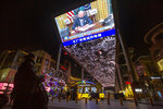 A vendor selling lighted balloons stands near a large video showing a government news report about the inauguration of President Joe Biden at a shopping mall in Beijing, Thursday, Jan. 21, 2021. China has expressed hope the Biden administration will improve prospects for people of both countries and give a boost to relations after an especially rocky patch, while getting in a few final digs at former Trump officials. (AP Photo/Mark Schiefelbein)