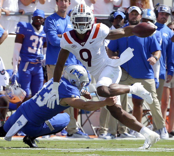 Virginia Tech wide receiver Tayvion Robinson (9) attempts to elude Middle Tennessee punter Kyle Ulbrich (13) in the first half of an NCAA college football game, Saturday, Sept. 11, 2021, in Blacksburg Va. (AP Photo/Matt Gentry)