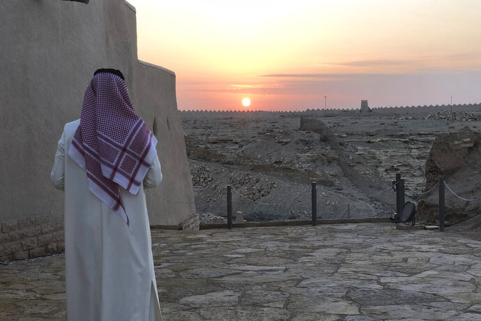 FILE - In this Dec. 16, 201, file photo, a man watches the sun setting over Dhiriyah, a UNESCO World Heritage site that includes a 17th-century fortress, mosques and clay-colored structures just outside of Saudi Arabia's capital of Riyadh. Saudi Arabia has announced a new tourist visa scheme Friday, Sept. 27, 2019, as part of efforts in the ultraconservative Muslim kingdom to diversify its economy and reduce dependence on oil. (AP Photo/Karin Laub, File)