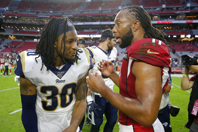 Los Angeles Rams running back Todd Gurley, left, greets Arizona Cardinals wide receiver Larry Fitzgerald after an NFL football game, Sunday, Dec. 1, 2019, in Glendale, Ariz. The Rams won 34-7. (AP Photo/Rick Scuteri)