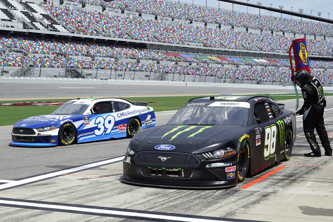 Riley Herbst (98) makes a quick stop for fuel as Ryan Sieg (39) gets out on pit road ahead of Herbst during the NASCAR Xfinity Series auto race at Daytona International Speedway, Saturday, Aug. 28, 2021, in Daytona Beach, Fla. (AP Photo/John Raoux)