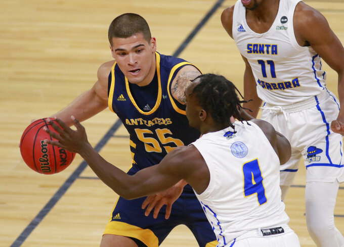 UC Irvine's Brad Greene (55) keeps the ball away from UC Santa Barbara's Devearl Ramsey (4) during the first half of an NCAA college basketball game for the championship of the Big West Conference men's tournament Saturday, March 13, 2021, in Las Vegas. (AP Photo/Ronda Churchill)