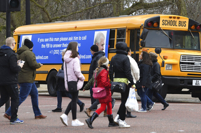 A yellow school bus with a message for the Britain's Prince Andrew, from US lawyer Gloria Allred, drives along The Mall towards Buckingham Palace in London Friday Feb. 21, 2020. Allred, who represents some of the accusers of Jeffrey Epstein, has been critical of the Prince Andrew for not speaking with the FBI about his former friend Epstein. Epstein died in a New York jail in August 2019 while he was awaiting trial on sex trafficking charges. U.S. authorities ruled the death a suicide. (Stefan Rousseau/PA via AP)