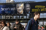 ADDS TRANSLATION OF BILLBOARD - People walk under an election campaign billboard for the Blue and White party, the opposition party led by Benny Gantz, in Ramat Gan, Israel, Tuesday, Feb. 18, 2020. The message next to Gantz, left, says