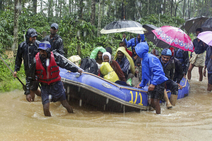 In this Friday, Aug. 9, 2019, photo, Indian army soldiers and volunteers transport flood victims to safer areas in Kodagu dictrict, in the southern Indian state of Karnataka. Flash floods and mudslides caused by days of torrential rains in the southern Indian states of Kerala and Karnataka have forced hundreds of thousands to move to relief camps. (AP Photo)