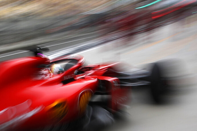 Ferrari driver Sebastian Vettel of Germany returns to his team's garage during the first practice session for the Chinese Formula One Grand Prix at the Shanghai International Circuit in Shanghai, Friday, April 13, 2018. (AP Photo/Andy Wong)