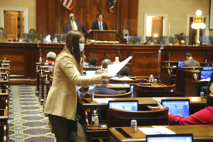 A page hands out committee assignments in the South Carolina House on Wednesday, Dec. 2, 2020, in Columbia, S.C. There were no real surprises in the committee assignments. (AP Photo/Jeffrey Collins)