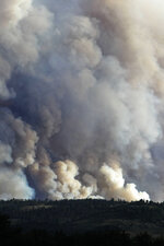 Smoke from a wildfire can be seen rising from the Medicine Bow National Forest from Highway 230 near Woods Landing, Wyo., Wednesday, June 13, 2018. Several thousand people in Colorado and Wyoming fled multiple wildfires scorching the drought-stricken U.S. West on Wednesday. (Shannon Broderck/Laramie Boomerang via AP)