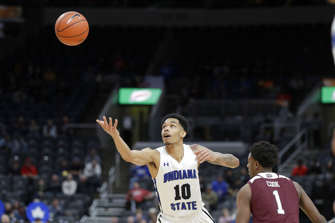 Indiana State's Christian Williams (10) reaches for the ball as Missouri State's Keandre Cook (1) defends during the first half of an NCAA college basketball game in the quarterfinal round of the Missouri Valley Conference men's tournament Friday, March 6, 2020, in St. Louis. (AP Photo/Jeff Roberson)