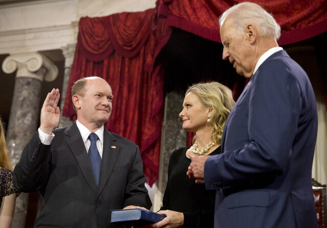 FILE - In this Jan. 6, 2015, file photo, Vice President Joe Biden administers the Senate oath to Sen. Chris Coons, D-Del., as Coons' wife, Annie Coons, watches during a ceremonial re-enactment swearing-in, in the Old Senate Chamber on Capitol Hill in Washington. When Coons speaks to the Democratic National Convention on Thursday, Aug. 20, before Biden's speech accepting the party's presidential nomination, his remarks will focus on faith — attesting in highly personal fashion to his longtime friend's belief in God. (AP Photo/Jacquelyn Martin, File)