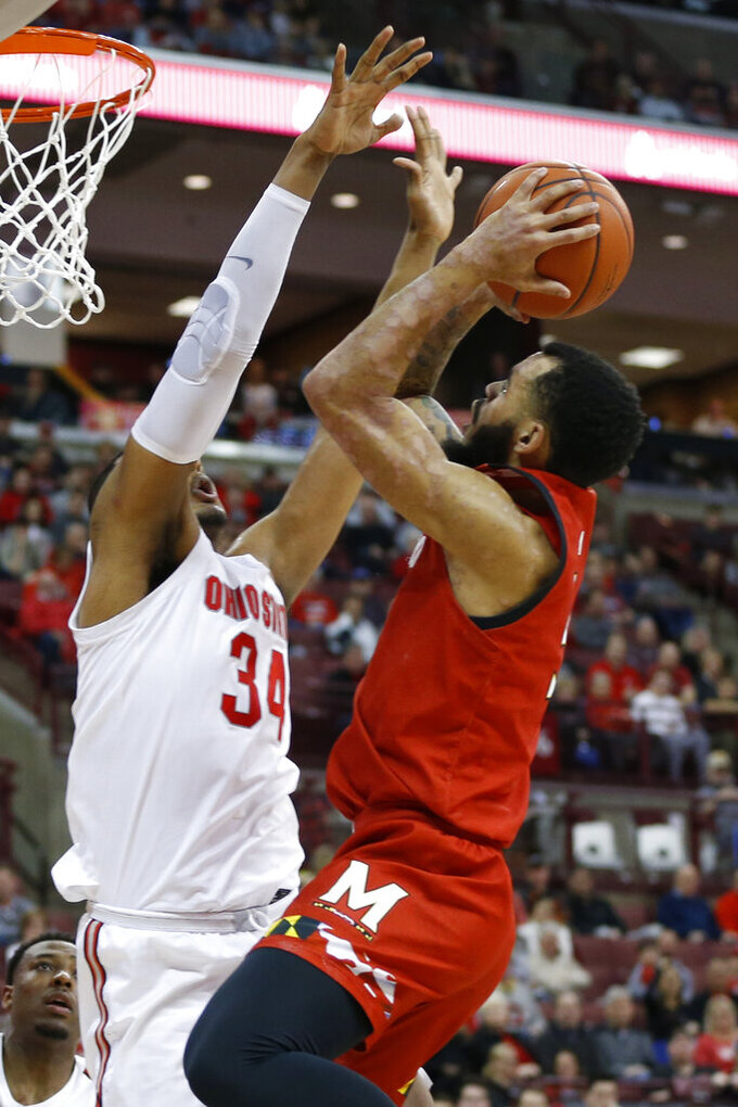 Maryland's Eric Ayala, right, shoots over Ohio State's Kaleb Wesson during the first half of an NCAA college basketball game Sunday, Feb. 23, 2020, in Columbus, Ohio. (AP Photo/Jay LaPrete)