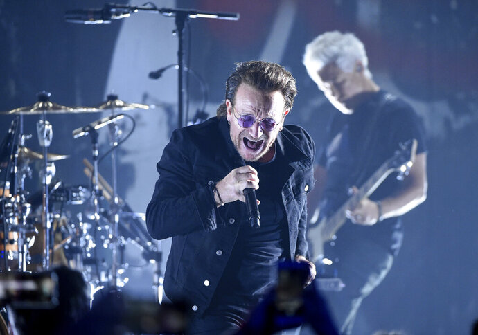 FILE - In this June 11, 2018 file photo,  Bono of U2 performs during a concert at the Apollo Theater in New York.  U2 raked in over $1 billion in sales to be named the artist of the decade by Pollstar. The touring trade publication tracks data on tours globally. It says U2 grossed $1.03 billion in ticket sales from November 2009 to November 2019. (Photo by Evan Agostini/Invision/AP, File)