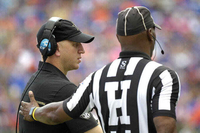 Vanderbilt head coach Clark Lea, left, talks with head linesman Ralph Green while a play is reviewed during the second half of an NCAA college football game against Florida, Saturday, Oct. 9, 2021, in Gainesville, Fla. (AP Photo/Phelan M. Ebenhack)