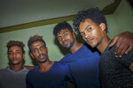 In this photo taken on Thursday, Oct. 10, 2019, from left, Eritrean under-20 soccer players Simon Asmelash Mekonen, Mewael Tesfai Yosief, Hermon Fessehaye Yohannes, and Hanibal Girmay Tekle talk together in a house where they are staying in Uganda. Four young players with Eritrea's national under-20 soccer team have defected during a tournament in Uganda, the latest players to leave one of the world's most tightly controlled regimes. (AP Photo)