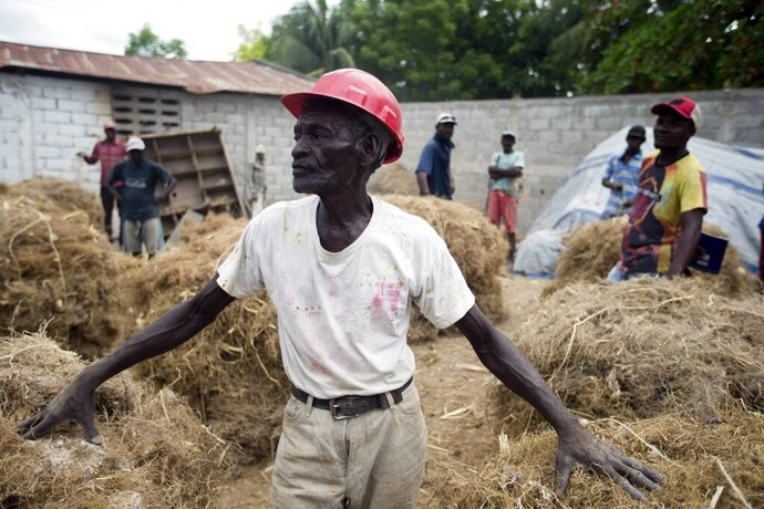 In this May 27, 2019 photo, Clerme Elmacide stands amid bales of vetiver roots at a plant in Les Cayes, Haiti. In the poorest country of the Western hemisphere, this is ground zero for a multimillion-dollar industry responsible for more than half the world's vetiver oil, an essential oil used in fine perfumes ranging from Chanel to Guerlain. (AP Photo/Dieu Nalio Chery)