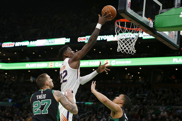 Phoenix Suns center Deandre Ayton (22) lays the ball up over Boston Celtics forward Daniel Theis (27) and forward Grant Williams (12) during the first half of an NBA basketball game, Saturday, Jan. 18, 2020, in Boston. (AP Photo/Mary Schwalm)